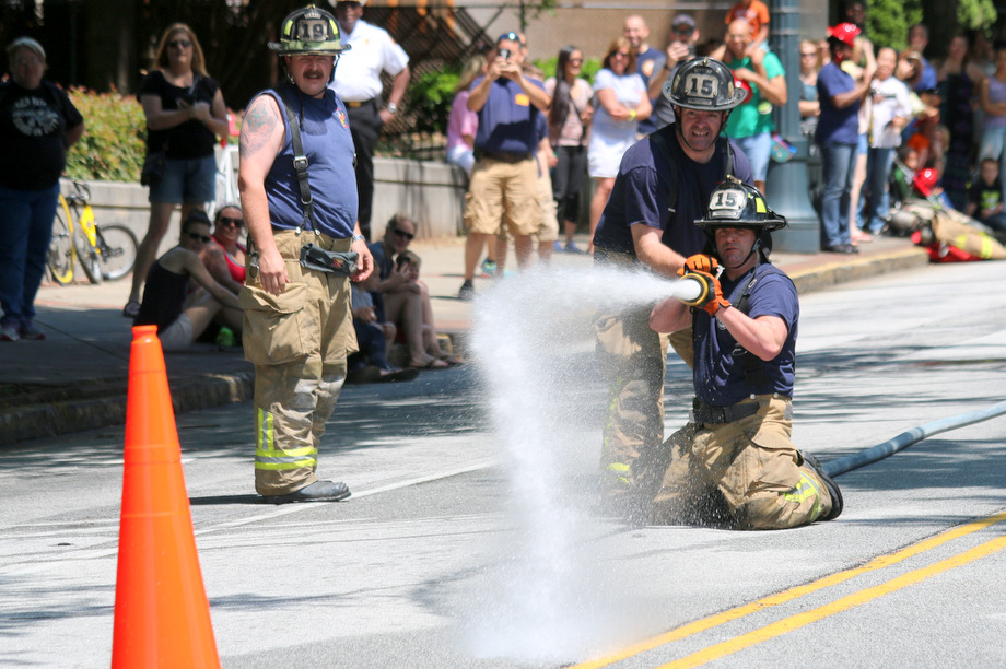 Firefighters participate in a fire rescue competition, known as Musters, during the 2015 Fire on the 4th festival on May 2, 2015, in the Old Fourth Ward section of Atlanta.